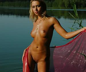 Beautiful nudist blonde girl is stripping at the lake