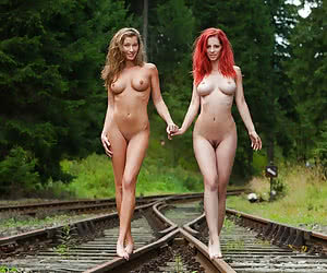 Cute young nudist girls posing in a railroad