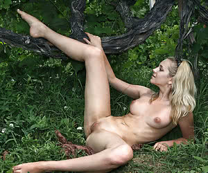 Young nudist models posing naked in a wild woods