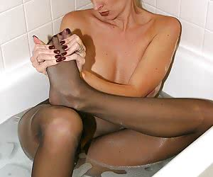 Seductive woman in brown pantyhose takes a bath
